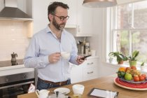 Человек, стоящий на кухне с чашечкой кофе, глядя на его смартфон — стоковое фото