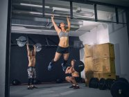 Three crossfit athletes training in gym together — Stock Photo
