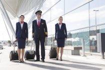 Pilota e hostess a piedi edificio esterno dell'aeroporto — Foto stock