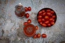 Vaso y botella de jugo de tomate y tazón de tomates frescos en la superficie de mala calidad - foto de stock