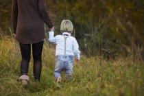 Mutter mit Sohn zu Fuß auf Wiese — Stockfoto