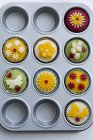 Cupcakes with colorful marzipan fondant in cupcake dish — Stock Photo