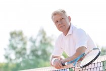 Portrait of tennis playerleaning on tennis net — Stock Photo