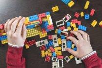 Mãos de crianças brincando com a construção de tijolos em uma tabela — Fotografia de Stock