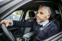 Portrait of man driving car looking aside — Stock Photo
