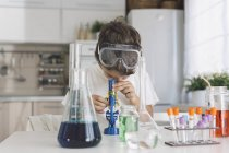 Boy playing science experiments at home looking through microscope — Stock Photo