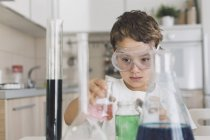 Boy playing science experiments at home — Stock Photo