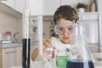 Мальчик играет научные эксперименты на дому — стоковое фото