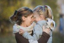 Смеющиеся мать и дочь на открытом воздухе — стоковое фото