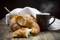 Croissants, fig jam and cup of hot coffee — Stock Photo