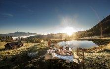 Austria, Salzburg State, Altenmarkt-Zauchensee, alpine pasture, breakfast at sunrise with woman sitting on background — Stock Photo