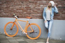 Woman leaning at wall beside bicycle — Stock Photo