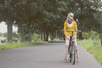 Woman on bicycle taking break in the park — Stock Photo