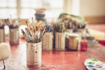Close-up of paintbrush in metal jar on table — Stock Photo