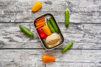 Spelt roll with cream cheese and carrots, bell peppers and cucumbers in metal box — Stock Photo