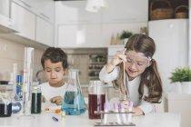 Junge und Mädchen spielen zu Hause naturwissenschaftliche Experimente — Stockfoto