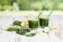 Стаканы зеленого смузи со шпинатом, огурцом, имбирем и яблоком на деревянном столе в саду — стоковое фото