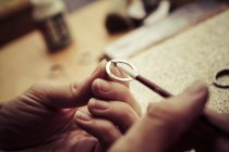 Goldsmith working on wedding rings, applying chemical on surface — Stock Photo