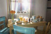 Portées de table du petit déjeuner contre fenêtre — Photo de stock