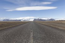 Iceland, Vatnajokull National Park, empty road with hills on background — Stock Photo