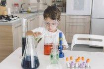 Garçon jouer des expériences scientifiques à la maison — Photo de stock