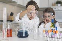 Niño y niña jugando experimentos científicos en casa - foto de stock
