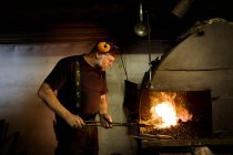 Blacksmith at work by the fireplace — Stock Photo