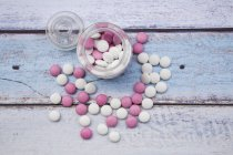 Glass of Bowl of pink and white chocolate buttons on wood — Stock Photo