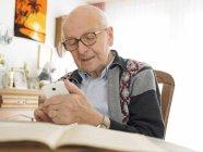 Старший людина сидить за столом і за допомогою мобільного телефону — стокове фото