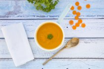 Top view of carrot soup in saucepan and sliced carrot — Stock Photo