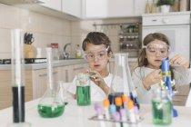 Garçon et fille jouant des expériences scientifiques à la maison — Photo de stock