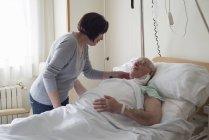 Старшая женщина, ухаживающая за мужем в больнице после операции — стоковое фото