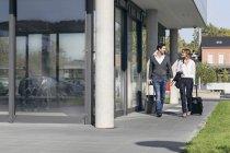 Deux hommes d'affaires avec des bagages, marchant sur la rue — Photo de stock