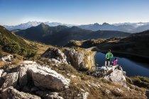 Австрия, Мбаппе, молодая пара с горными велосипедами отдыхает на скале в горах — стоковое фото