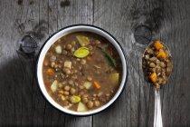 Linsen und Gemüse Suppe mit Löffel auf graues Holz — Stockfoto