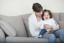 Woman with her daughter on couch — Stock Photo