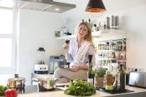 Femme dans la cuisine buvant du vin — Photo de stock