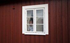 Norwegen, Lofoten, Frau Blick durch Fenster — Stockfoto