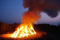 Gens qui regardent le feu de joie de Pâques dans la nuit — Photo de stock