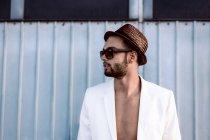 Jeune homme, portant chapeau et des lunettes de soleil et veste blanche sur la poitrine nue — Photo de stock