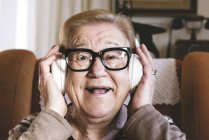 Retrato de uma senhora idosa feliz ouvindo música com fones de ouvido — Fotografia de Stock