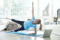 Woman with laptop exercising — Stock Photo