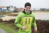 Portrait of smiling jogger running outdoors — Stock Photo