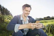 Uomo sorridente seduto su un prato e utilizzando il telefono cellulare — Foto stock