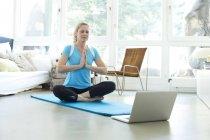 Женщина с ноутбуком практикующая йогу — стоковое фото