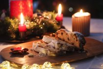 Sliced Stollen and lighted candles at Advent season — Stock Photo