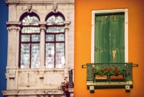 Italy, Venice, house facade with closed shutters and palazzo in the background — Stock Photo