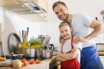Portrait of father and son in the kitchen smiling at camera — Stock Photo