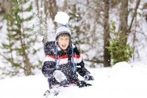 Happy boy throwing a snowball in the woods — Stock Photo