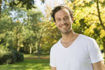 Portrait of smiling man standing in a park and looking at camera — Stock Photo